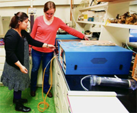 Farah Abedin and Sarah Waldo adjust equipment during an atmospheric composition lab.